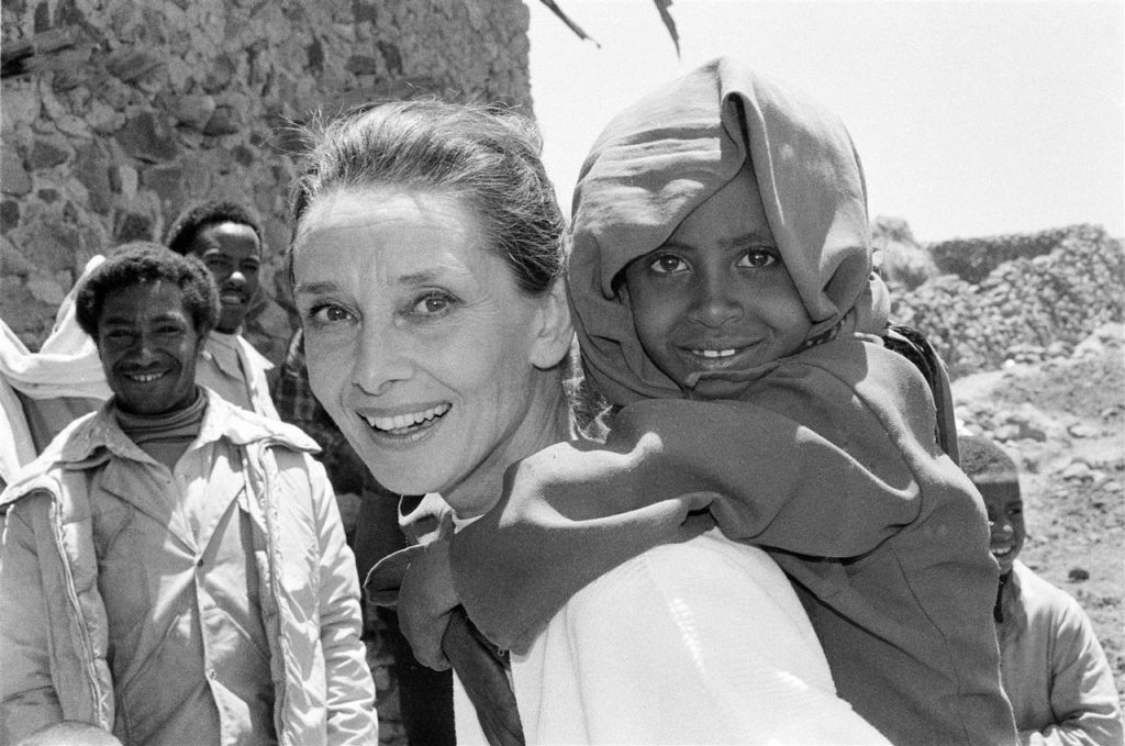 Audrey Hepburn carries a child